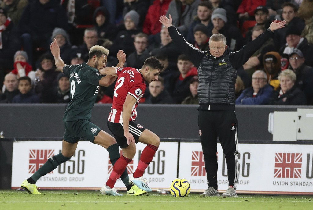 Newcastle United's Joelinton, left, challenges Sheffield United's George Baldock in front of Sheffield United manager Chris Wilder during their Englis...