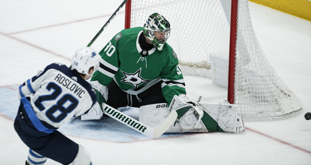 Dallas Stars goaltender Ben Bishop (30) deflects a shot from Winnipeg Jets forward Jack Roslovic (28) during the first period an NHL hockey game Thurs...