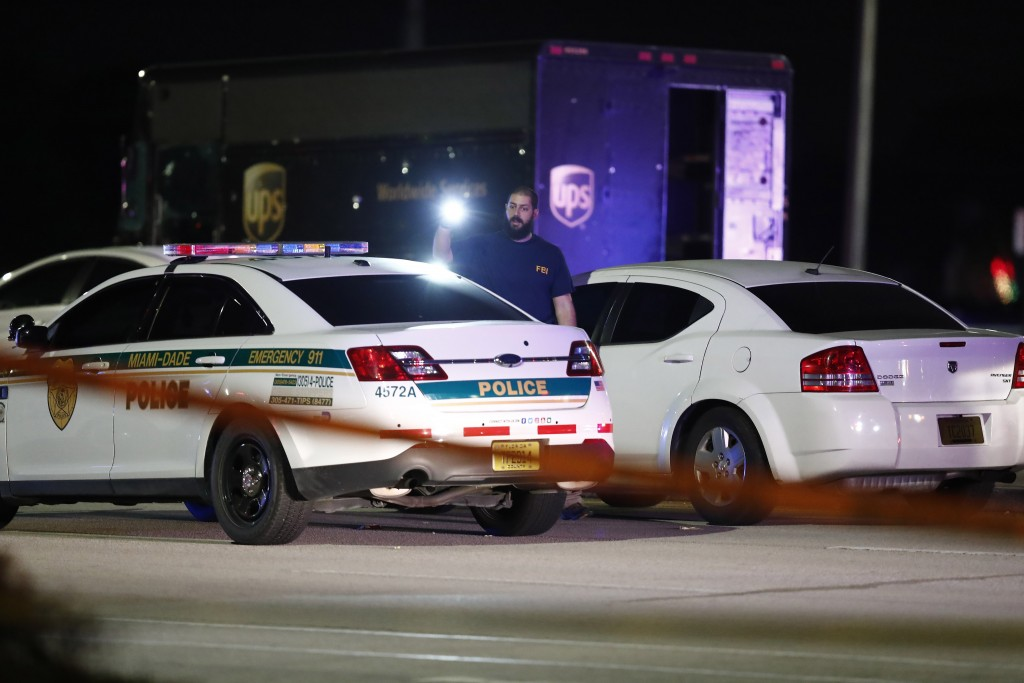 An FBI official investigates the scene of a shooting, Thursday, Dec. 5, 2019, in Miramar, Fla. Four people, including a UPS driver, were killed Thursd...