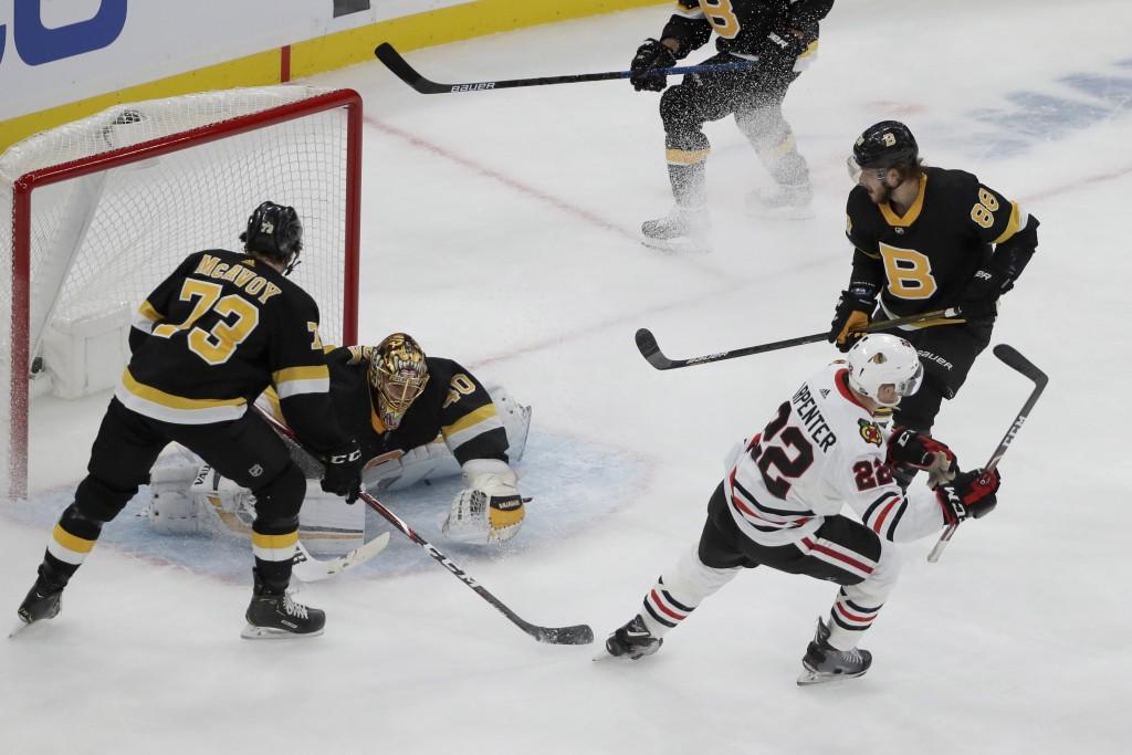 Chicago Blackhawks center Ryan Carpenter (22) starts to celebrate his goal against Boston Bruins goaltender Tuukka Rask (40) as Bruins defenseman Char...