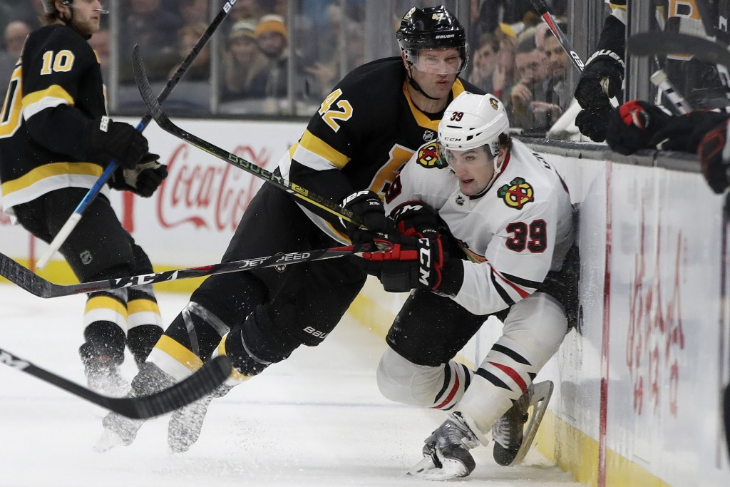 Boston Bruins right wing David Backes (42) checks Chicago Blackhawks defenseman Dennis Gilbert (39) into the boards in the second period of an NHL hoc...