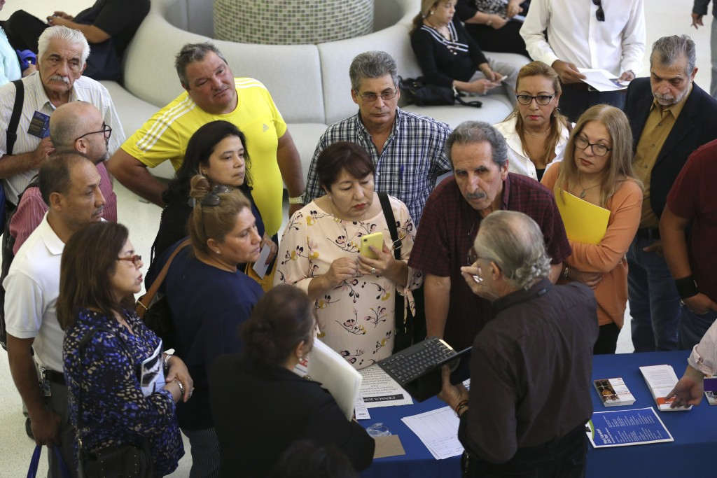 FILE - In this Sept. 18, 2019, file photo people inquire about temporary positions available for the 2020 Census during a job fair designed for people...