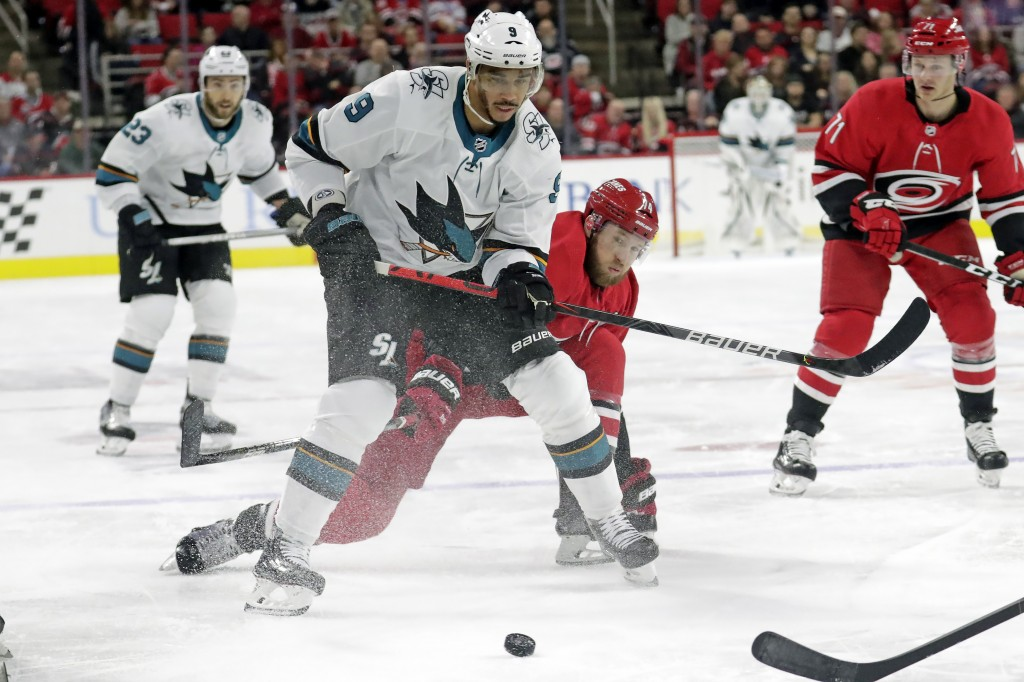 San Jose Sharks' Evander Kane (9) and Carolina Hurricanes' Jaccob Slavin (74) battle for the puck during the first period of an NHL hockey game in Ral...