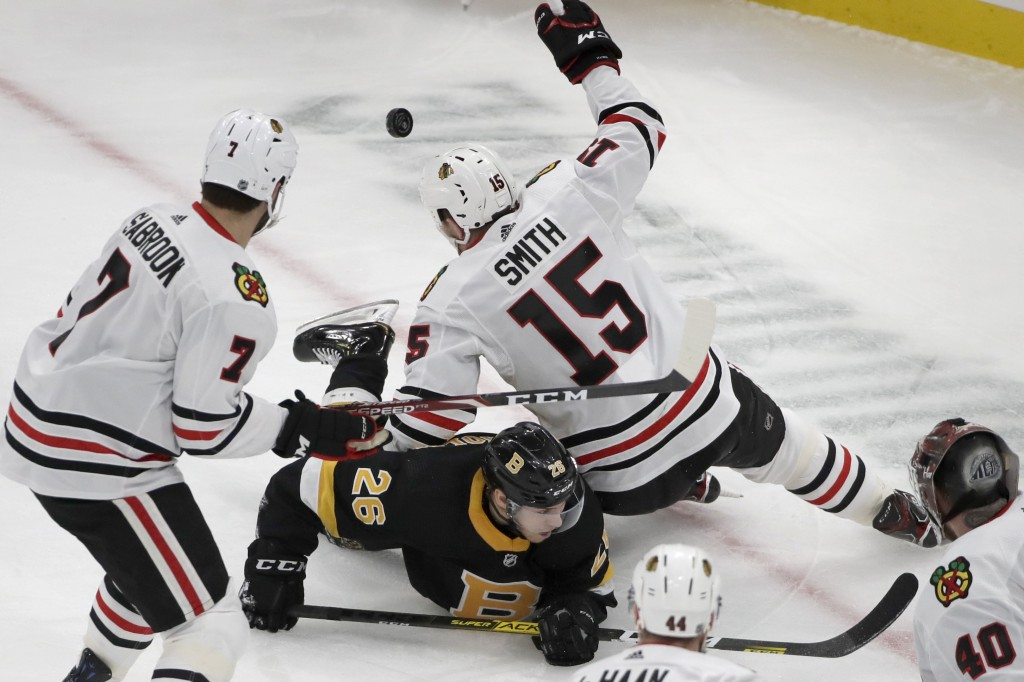 Boston Bruins center Par Lindholm (26) goes down as he competes for the puck against Chicago Blackhawks center Zack Smith (15) in the first period of ...