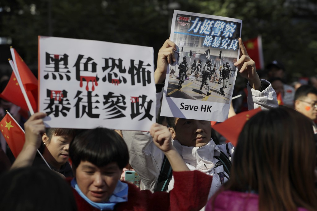 """Pro-Beijing supporters hold up signs which reads """"Black Terror, Rioters involved in politics"""" and """"Support Police, Get rid of Violence"""" during a rally..."""