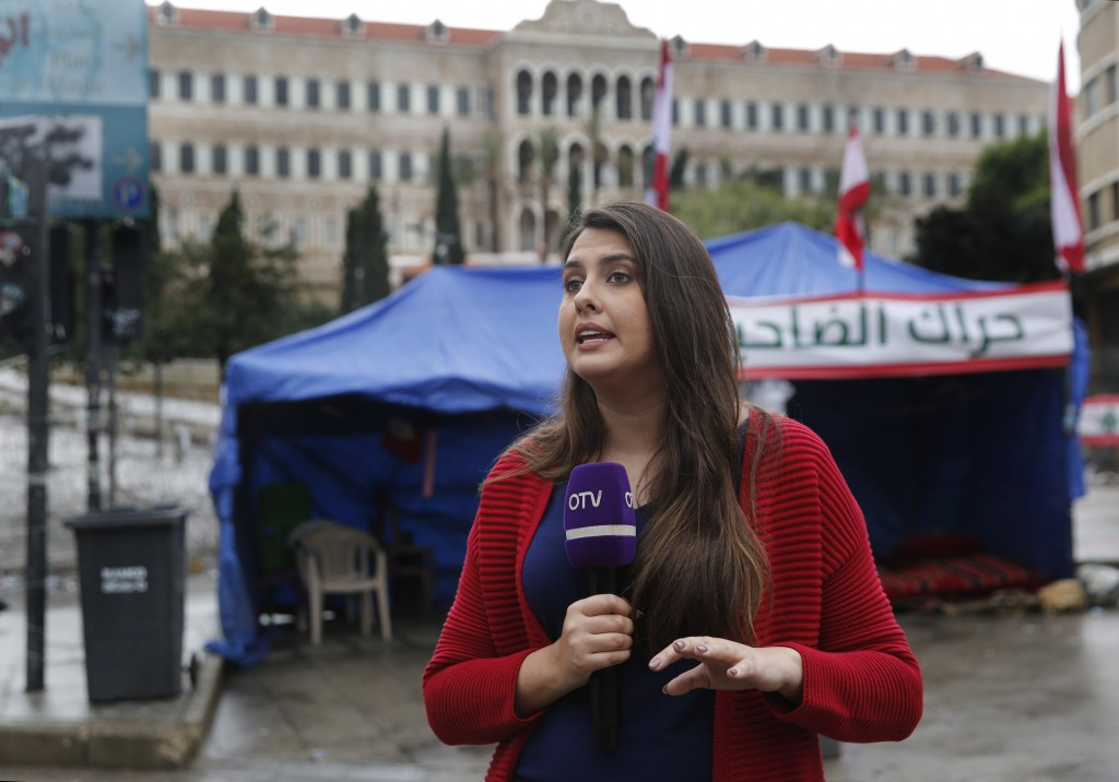In this Thursday, Dec. 5, 2019 photo, Rima Hamdan, a Lebanese reporter for OTV a station that is backed by Lebanese President Michel Aoun, reports fro...