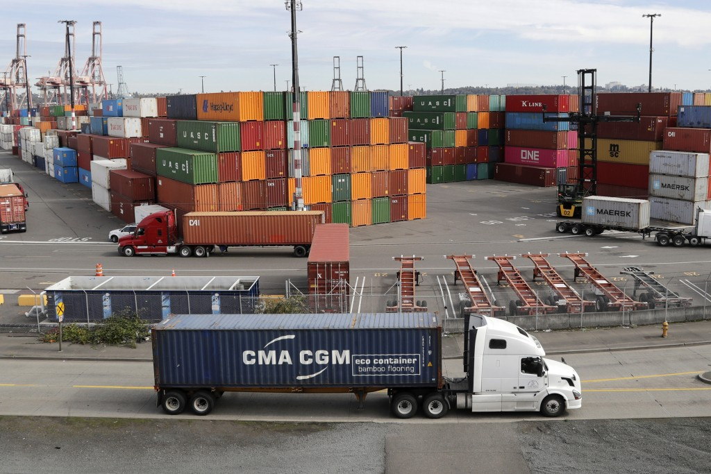 FILE - In this Oct. 2, 2019, file photo trucks hauling shipping containers drive near containers stacked five-high at a terminal on Harbor Island in S...