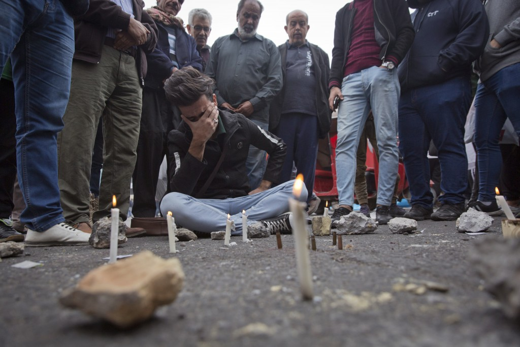 Iraqis gather around a crying man who lit candles by the spot where an Iraqi protester was killed Friday, at Khilani square, in Baghdad, Iraq, Saturda...