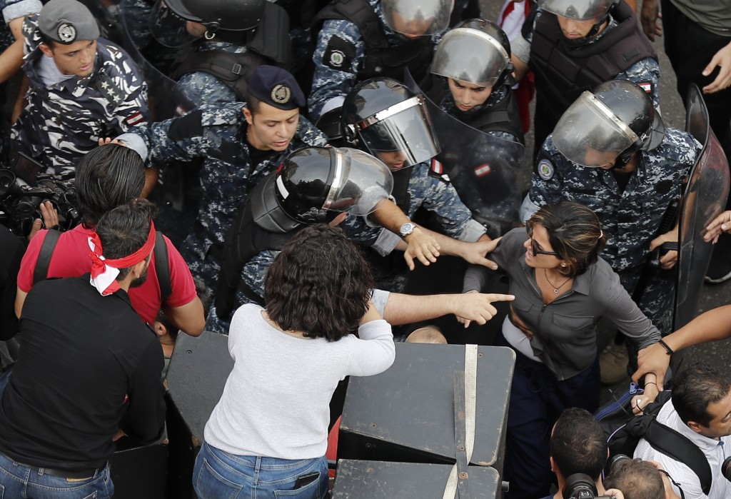 In this Friday Oct. 25, 2019,  MTV television reporter Nawal Berry, right, is protected by riot policemen after she was attacked by Shiite supporters ...