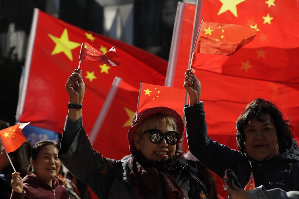 Pro-Beijing supporters wave the Chinese national flags during a rally in Hong Kong on Saturday, Dec. 7, 2019. Six months of unrest have tipped Hong Ko...