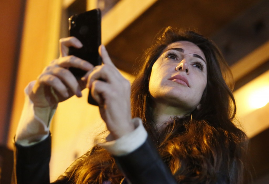 In this Wednesday, Dec. 4, 2019 photo, Lebanese anchorwoman Dima Sadek uses her cellphone to film an anti-government protest, in Beirut, Lebanon. Sade...
