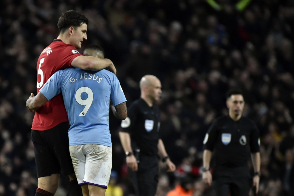 Manchester United's Harry Maguire, left, and Manchester City's Gabriel Jesus react at the end of the English Premier League soccer match between Manch...