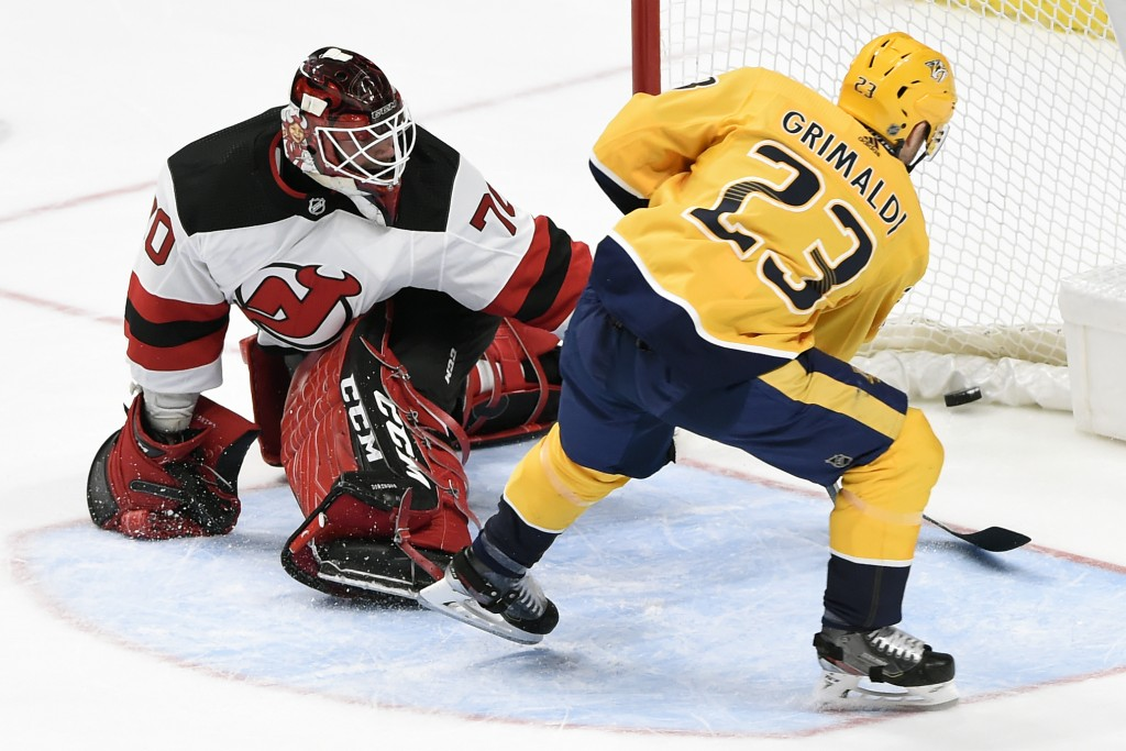 Nashville Predators right wing Rocco Grimaldi (23) scores against New Jersey Devils goaltender Louis Domingue (70) during the third period of an NHL h...