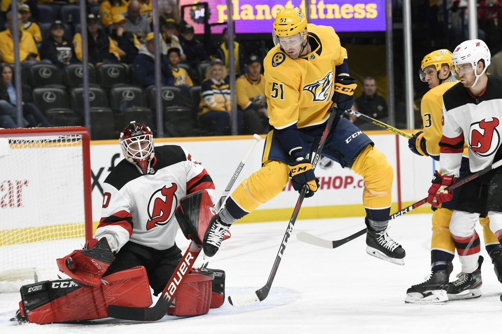 Nashville Predators left wing Austin Watson (51) jumps out of the way as New Jersey Devils goaltender Louis Domingue (70) gloves a shot during the sec...