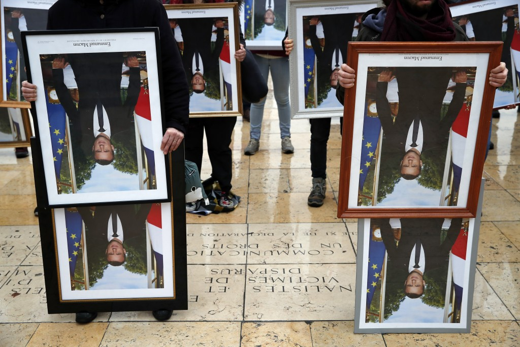 A hundred activists hold portraits of President Emmanuel Macron to urge France to take action during the U.N. COP 25 climate talks in Madrid, during a...