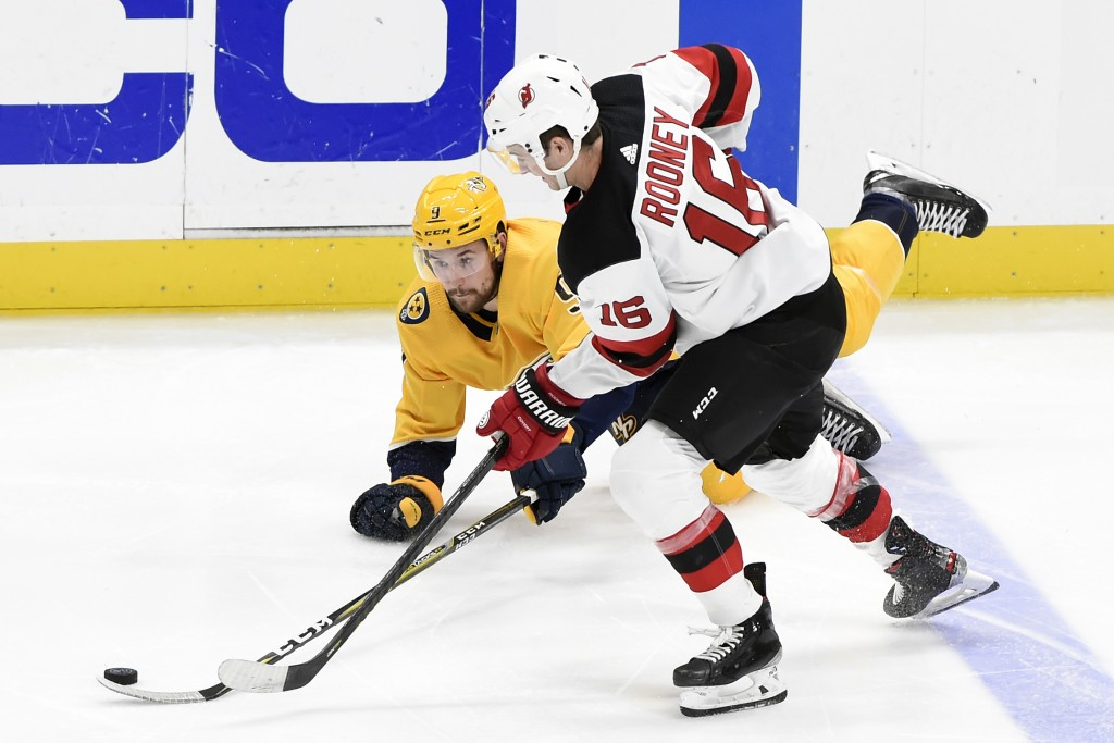 Nashville Predators left wing Filip Forsberg (9), of Sweden, clears the puck away from New Jersey Devils center Kevin Rooney (16) during the third per...