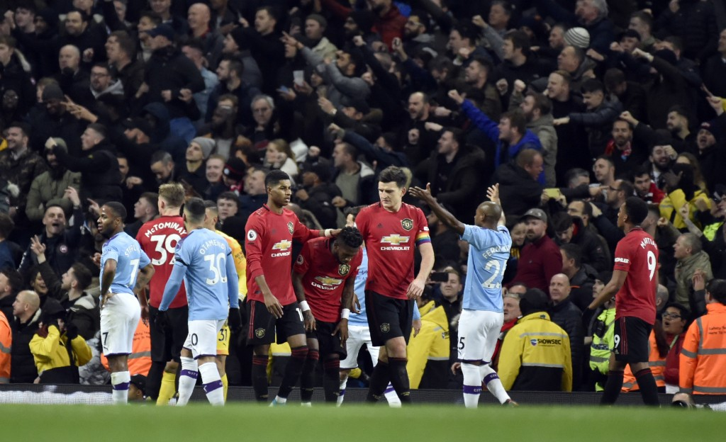 Players react to items thrown by Manchester City fans during the English Premier League soccer match between Manchester City and Manchester United at ...