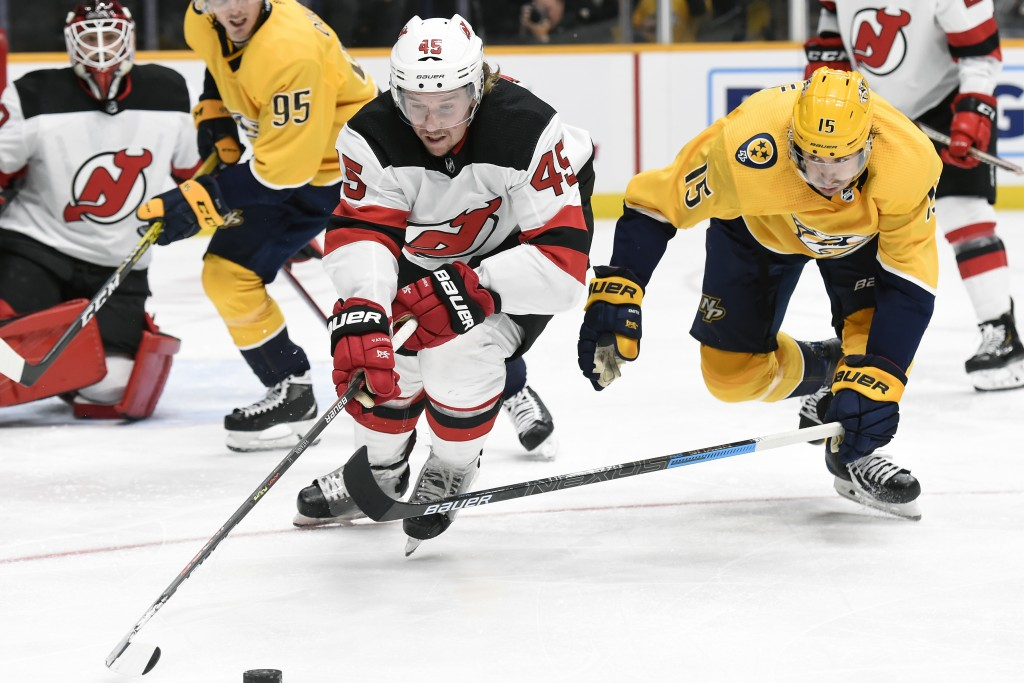 New Jersey Devils defenseman Sami Vatanen (45), of Finland, and Nashville Predators right wing Craig Smith (15) chase the puck during the second perio...