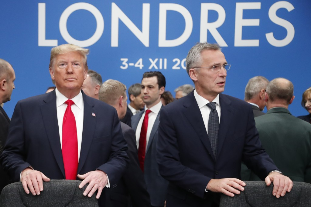 In this Dec. 4, 2019, photo, U.S. President Donald Trump and NATO Secretary General Jens Stoltenberg wait to take their seats prior to a NATO leaders ...