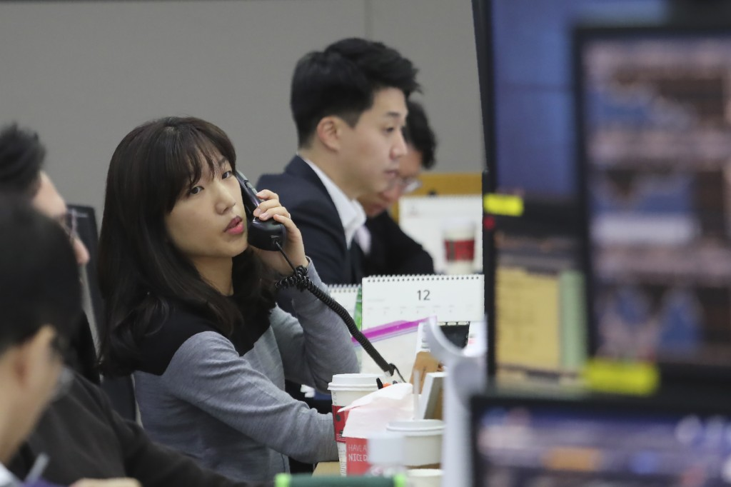 A currency trader talks on the phone at the foreign exchange dealing room of the KEB Hana Bank headquarters in Seoul, South Korea, Monday, Dec. 9, 201...