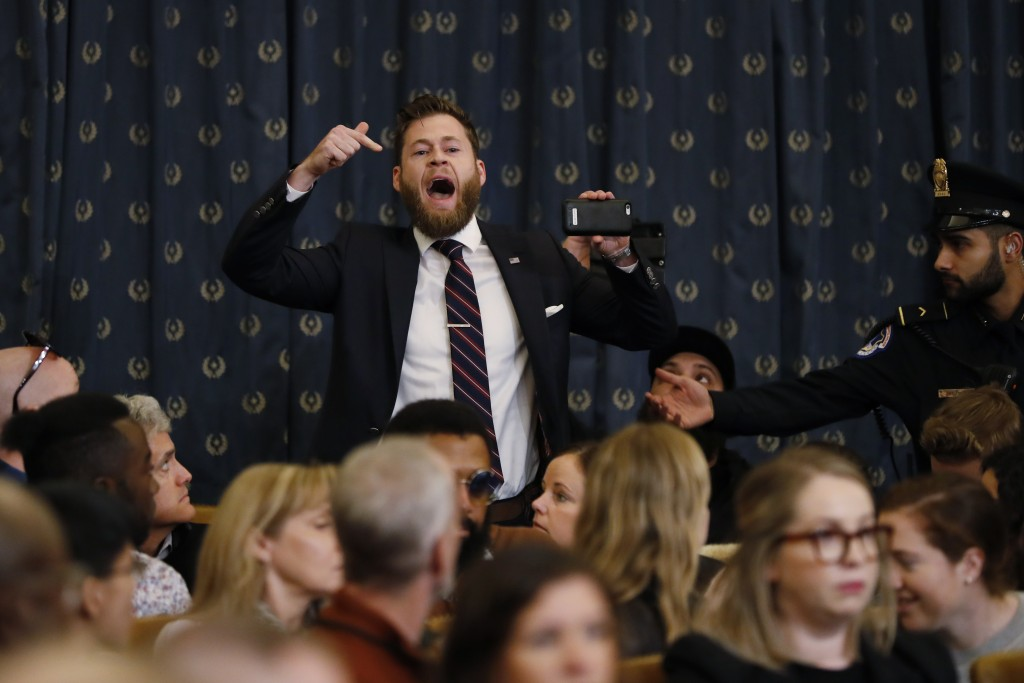 A protestor speaks out as the House Judiciary Committee hears investigative findings in the impeachment inquiry of President Donald Trump, Monday, Dec...