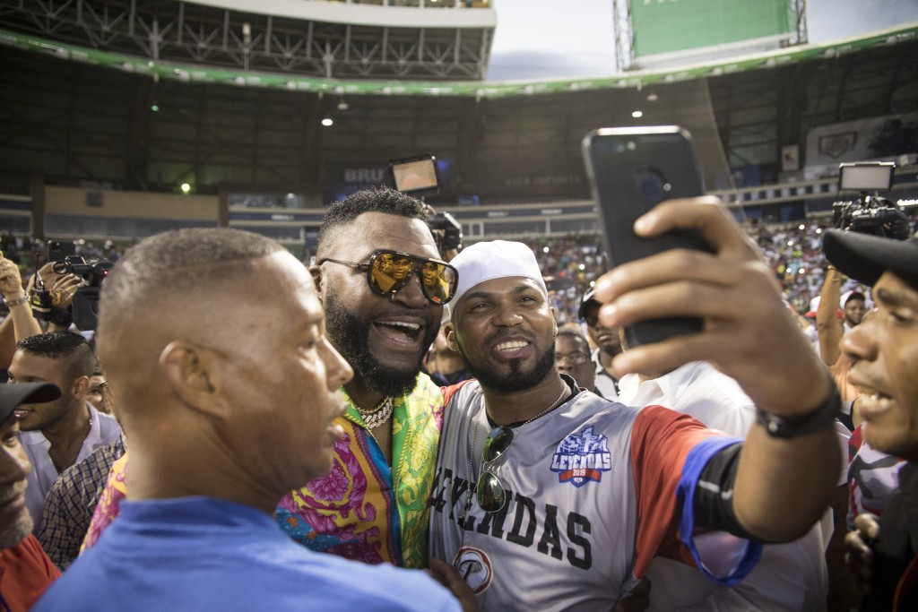Legendary Boston Red Sox slugger David Ortiz poses for a photo with a fan after making a surprise appearance at the Day of Legends baseball event at t...