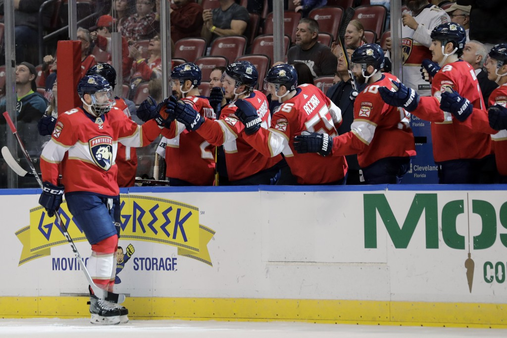 Florida Panthers' Keith Yandle, left, celebrates with teammates after scoring a goal during the first period of an NHL hockey game against the San Jos...