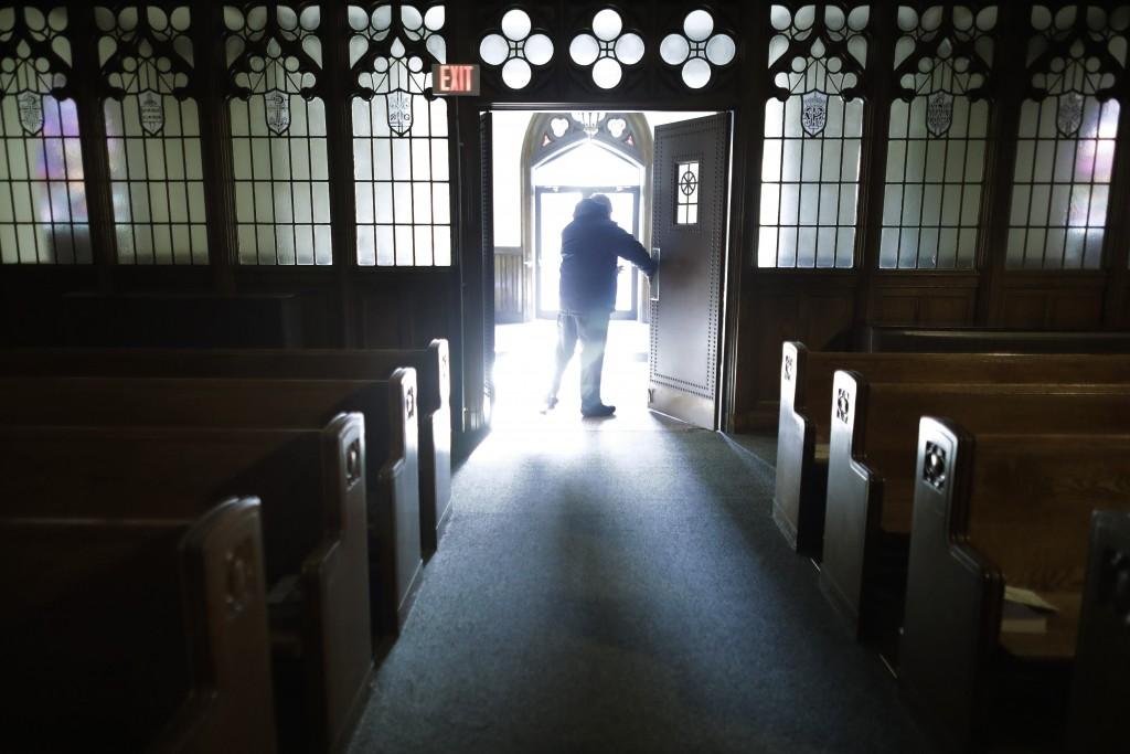 In this Saturday, Nov. 9, 2019 photo, Rev. Mark Stelzer, administrator of St. Jerome's Parish, in Holyoke, Mass., opens doors to the Catholic church b...