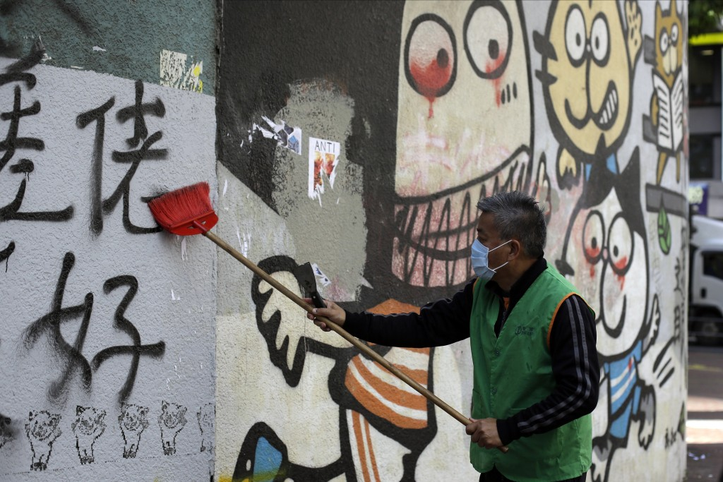A worker cleans up a vandalized wall Monday, Dec. 9, 2019, in Hong Kong. Hundreds of thousands of demonstrators crammed into Hong Kong's streets on Su...