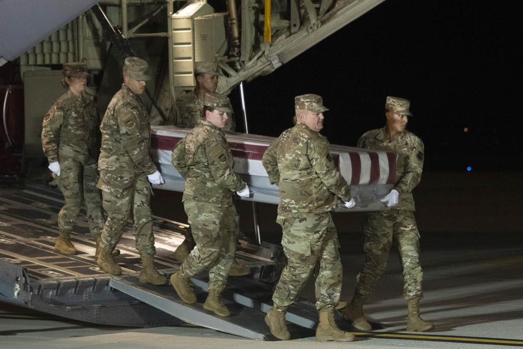 An Air Force carry team moves a transfer case containing the remains of Navy Ensign Joshua Watson on Sunday, Dec. 8, 2019, at Dover Air Force Base, De...