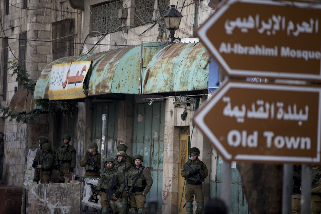 Israeli troops take their position during clashes with Palestinian demonstrators during a protest over Israeli settlement activity Monday, Dec. 9, 201...