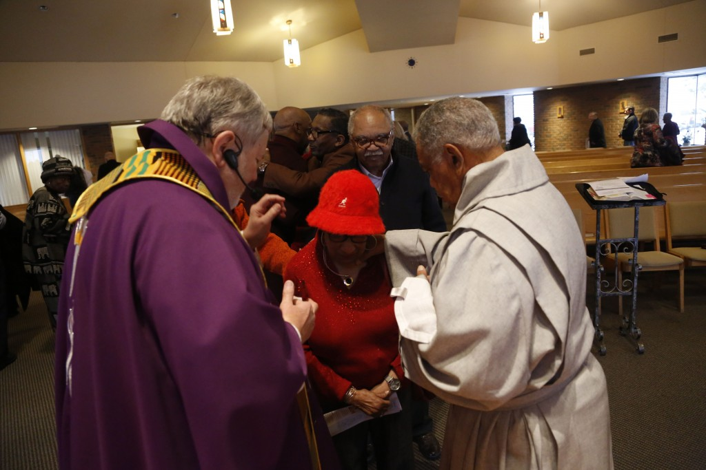 In this Sunday, Dec. 1, 2019 photo, Rev. Philip Schmitter anoints a parishioner after Mass at Christ the King Catholic Church in Flint, Mich. Schmitte...