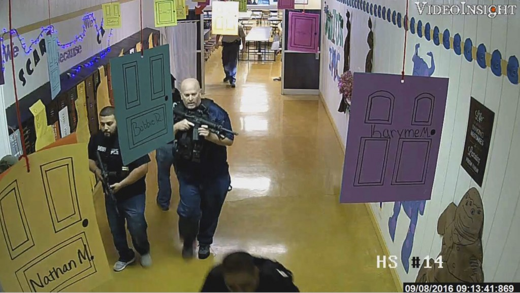In this still frame image taken from video provided by the Texas Rangers and recorded on Sept. 8, 2016, armed law enforcement officers move through a ...