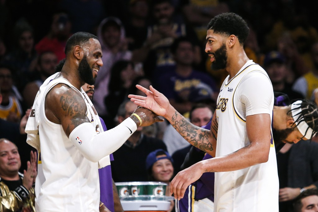Los Angeles Lakers' LeBron James, left, celebrates with teammate Anthony Davis during a timeout in the second half of an NBA basketball game, Sunday, ...