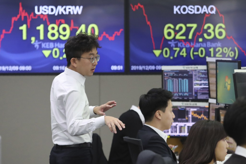 A currency trader gestures at the foreign exchange dealing room of the KEB Hana Bank headquarters in Seoul, South Korea, Monday, Dec. 9, 2019. Asian s...