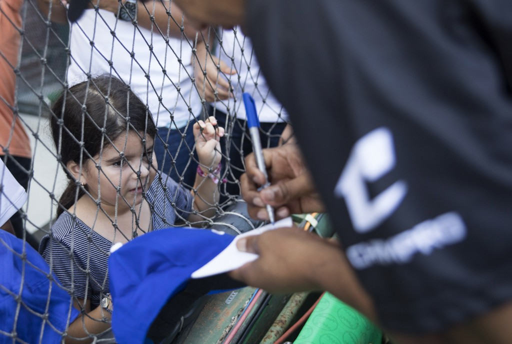A child watches as retired Dominican professional Major League pitcher Octavio Dotel autographs her baseball cap during the Day of Legends event at th...
