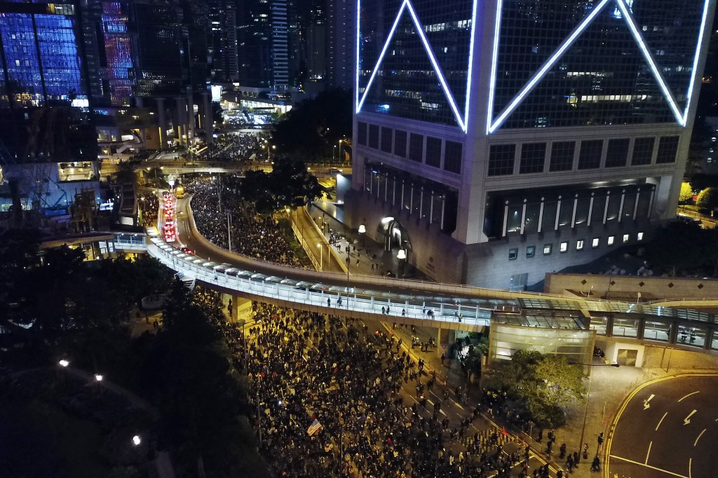 In this Sunday, Dec. 8, 2019, photo, pro-democracy protesters march into the night in central Hong Kong. Hundreds of thousands thronged Hong Kong stre...