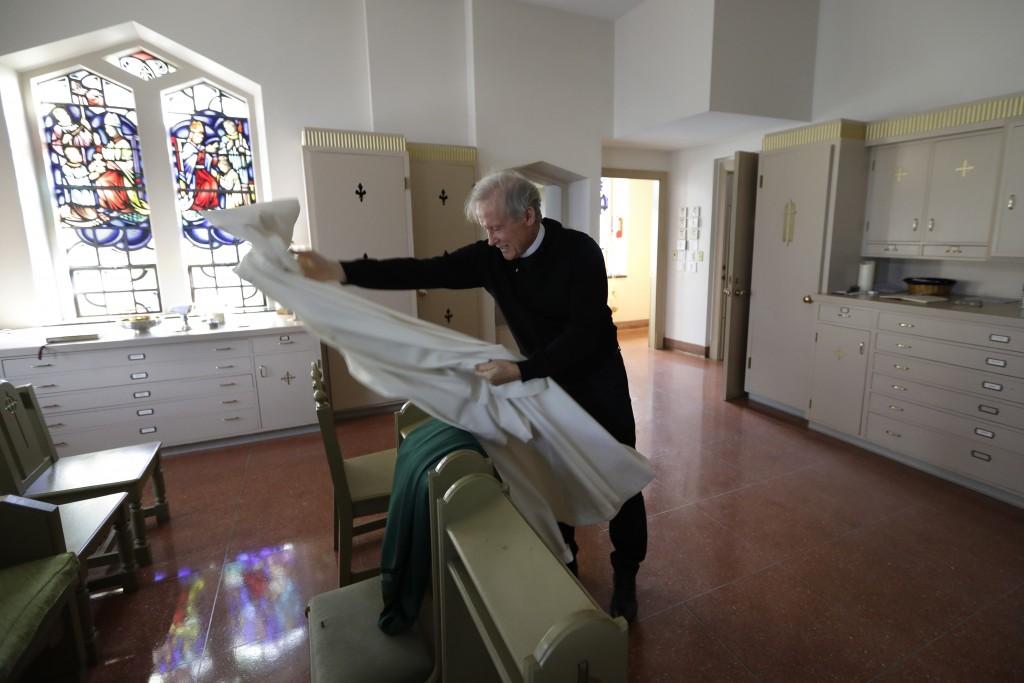 In this Sunday, Oct. 20, 2019 photo, Rev. William Tourigny, 66, pastor of St. Rose de Lima Parish, in Chicopee, Mass., arranges vestments while prepar...
