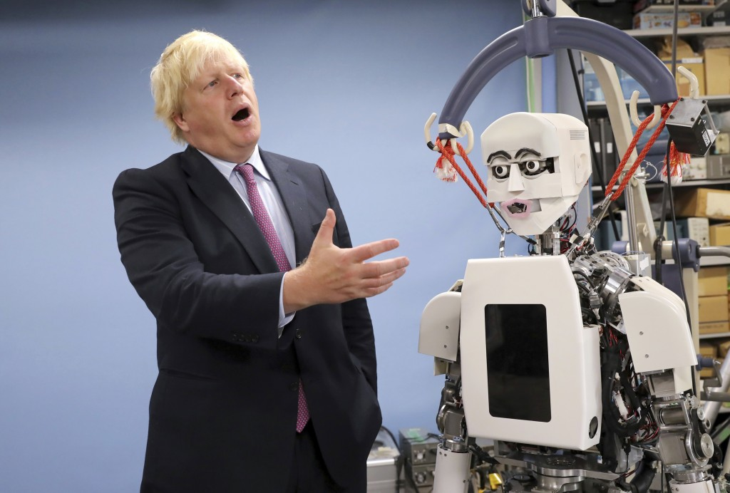 FILE - In this Thursday, July 20, 2017 file photo Britain's Foreign Secretary Boris Johnson gestures as he looks at a humanoid robot at Research Insti...