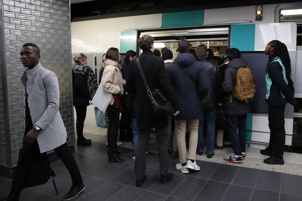 Commuters try to enter a subway train Tuesday, Dec. 10, 2019 in Paris. Only about a fifth of French trains ran normally Tuesday, frustrating tourists ...