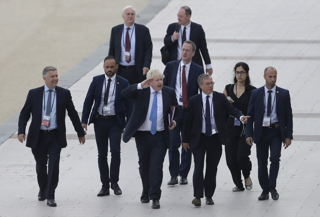 FILE - In this Monday, Aug. 26, 2019 file photo Britain's Prime Minister Boris Johnson, center, salutes people as he walks along the seafront in Biarr...