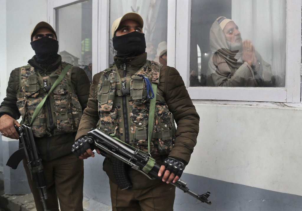 FILE- In this, Nov. 10, 2019 file photo, Indian policemen guard and Kashmiri Muslims pray as the head priest displays a relic of Islam's Prophet Muham...