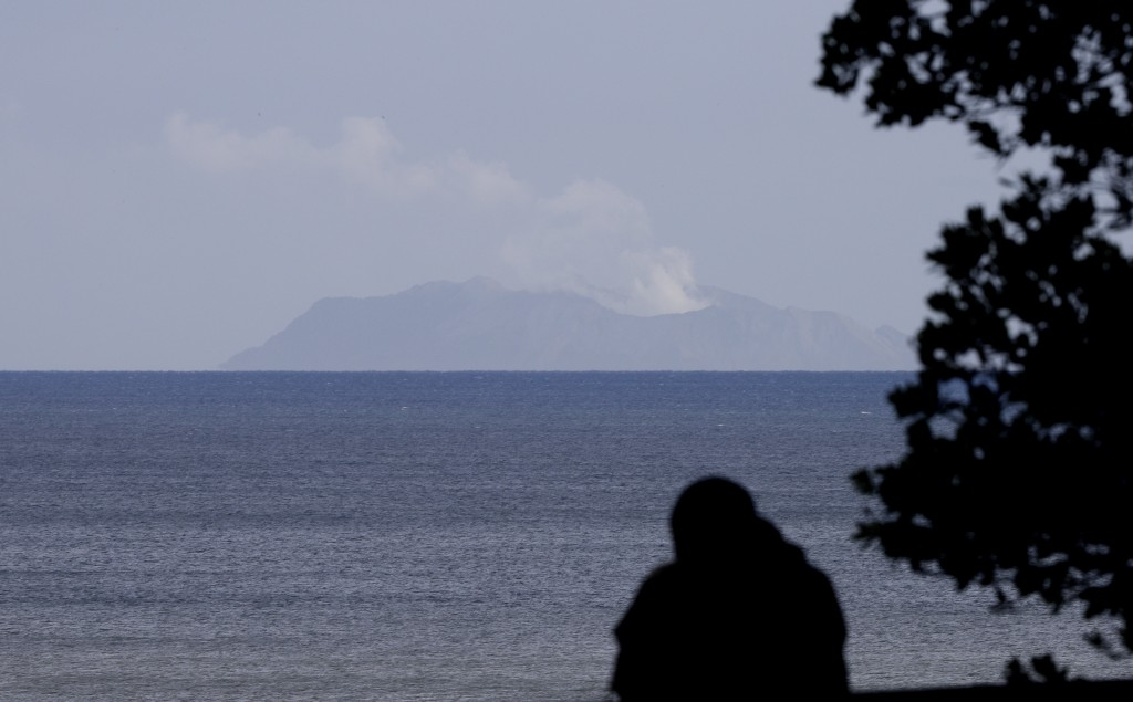 A man watches as a plume of steam is seen above White Island early morning off the coast of Whakatane, New Zealand, Tuesday, Dec. 10, 2019. A volcanic...