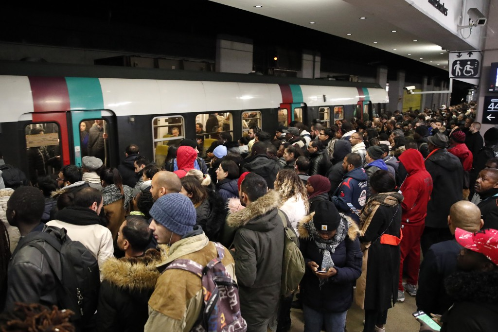 Commuters wait to catch a subway train Tuesday, Dec. 10, 2019 in Paris. Only about a fifth of French trains ran normally Tuesday, frustrating tourists...