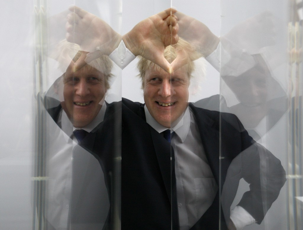 FILE - In this Friday, Jan. 14, 2011 file photo Boris Johnson, then Mayor of London in seen looking through perspex as models of the next two commissi...