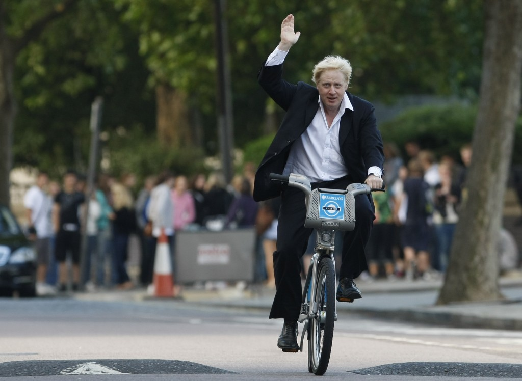 FILE - In this Friday, July 30, 2010 file photo Boris Johnson Mayor of London waves to the media as he helps launch a new cycle hire scheme in London....