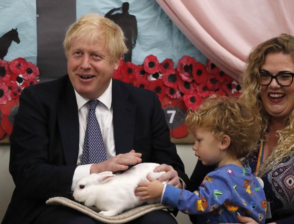 FILE - In this Thursday, Nov. 14, 2019 file photo Britain's Prime Minister Boris Johnson hold Rosie the rabbit during a visit of the West Monkton CEVC...