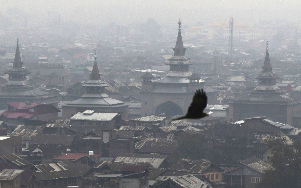 In this Nov. 20, 2019 photo, a bird flies as minarets of grand Jamia Masjid, the main Mosque is seen in center of the city in Srinagar, Indian control...