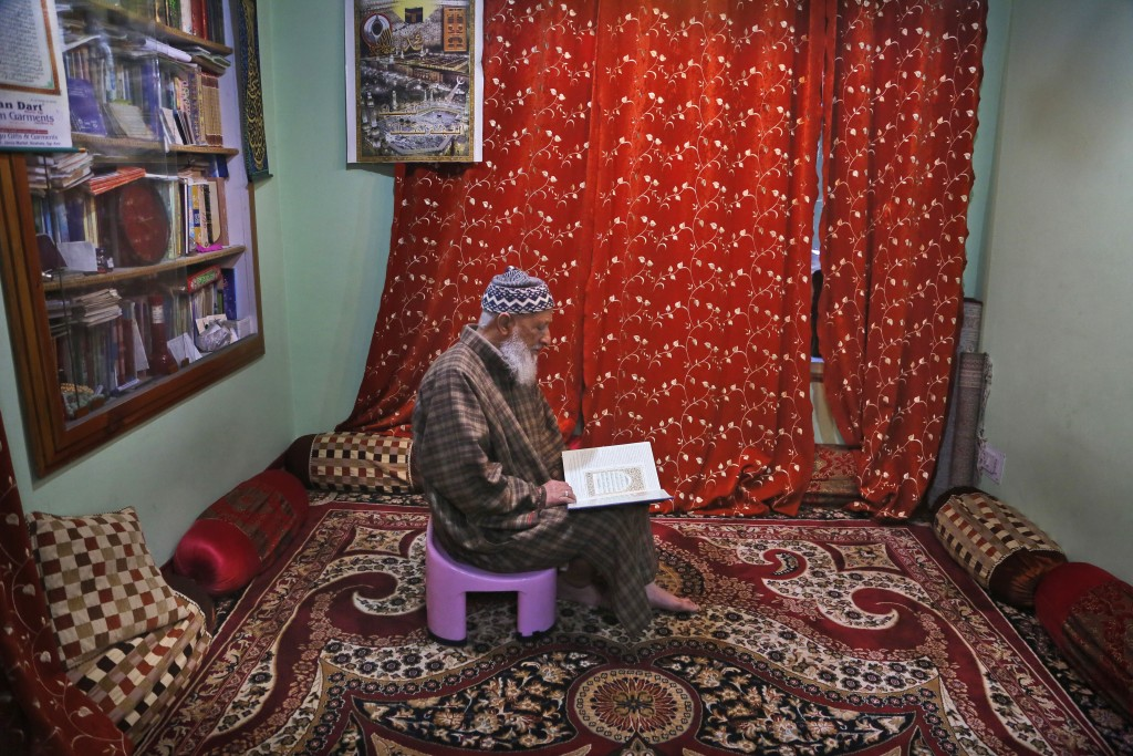 In this Nov. 19, 2019 photo, Mohammed Yasin Bangi, muezzin at grand Jamia Masjid, city's main mosque reads holy Quran inside his home in Srinagar, Ind...