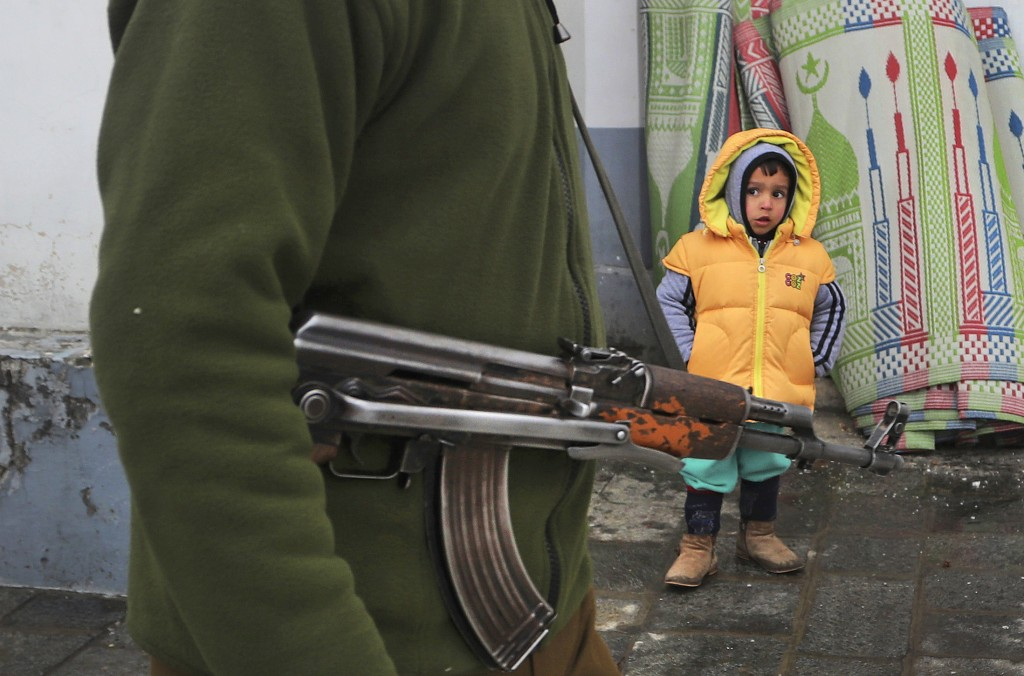 FILE- In this, Nov. 10, 2019 file photo, an Indian policeman guards as a Kashmiri child looks on outside the Hazratbal shrine, on the occasion of the ...
